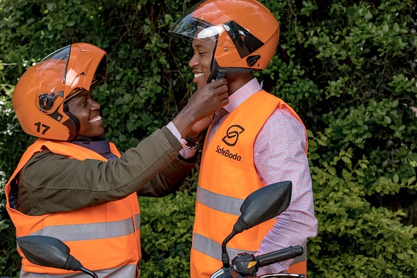A SafeBoda rider helps a passenger wear a helmet