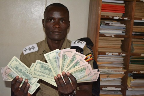 A police officer with some of the counterfeit notes