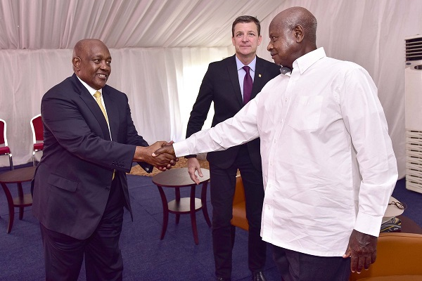 President Museveni shakes hands with MTN Uganda Chairman Charles Mbire as Rob Shuter looks on
